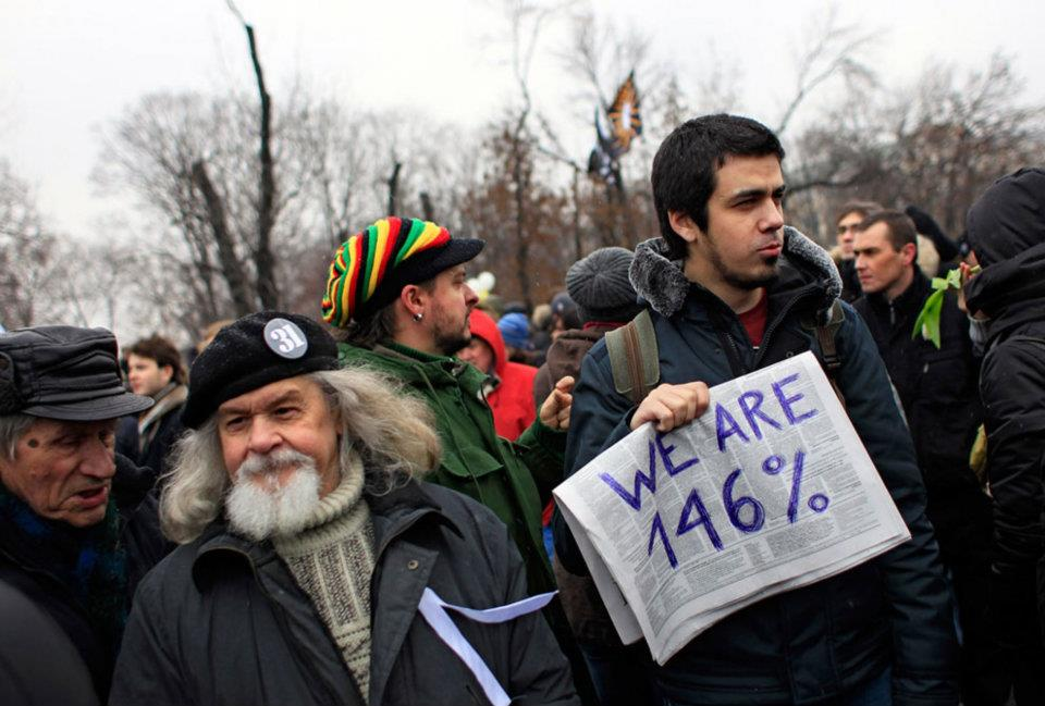 """Protesters, during a mass rally to protest against the vote rigging in Russia's parliamentary elections, in Moscow, on December 10, 2011. The """"146%"""" refers to a screen capture from a Russian news broadcast that spread across the internet, appearing to show total votes for all of the parties adding up to 146% (as well as the Occupy Wall Street movement's """"We are the 99%"""")"""