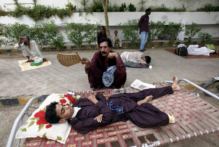 A man uses a hand-held fan to cool down his son, while waiting for their turn for a medical checkup, outside Jinnah Postgraduate Medical Centre (JPMC) during intense hot weather in Karachi, Pakistan, June 23, 2015. An intense heat wave over three days has killed more than 180 people in Pakistan's southern Sindh province, officials said on Monday, leading authorities to declare an emergency as the electricity grid crashed and bodies stacked up in the morgues. REUTERS/Akhtar Soomro   - RTX1HO6O